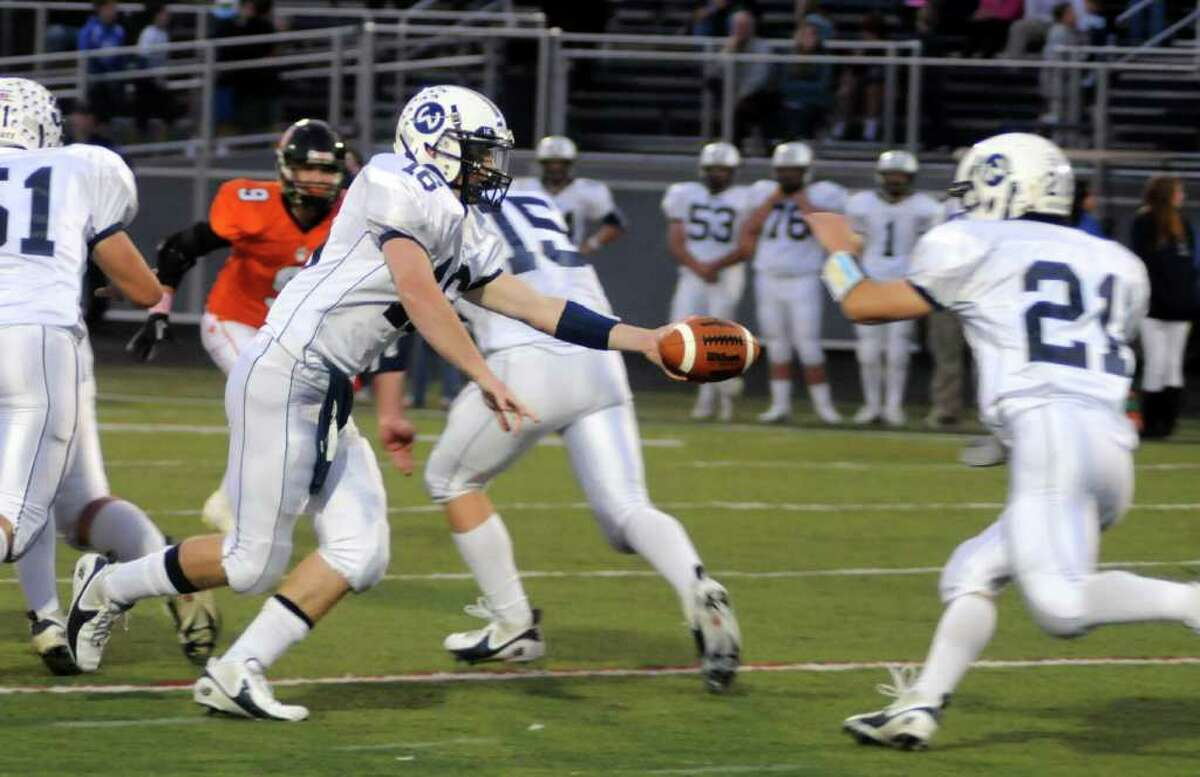 Wilton's QB #16 Sean Carroll hands the ball off to his teammate, Travis Stella, during Thursday nights game against Ridgefield at Wilton High School on Oct. 6,2011.