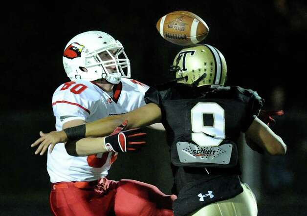 At left, receiver Joe Kelly, # 80 of Greenwich High School, gets a bounce off the helmet of Trumbull High School defender Matt Nakano, # 9, to make a reception during football game between Greenwich High School and Trumbull High School at Trumbull High School, Thursday night, Oct. 6, 2011. Photo: Bob Luckey / Greenwich Time