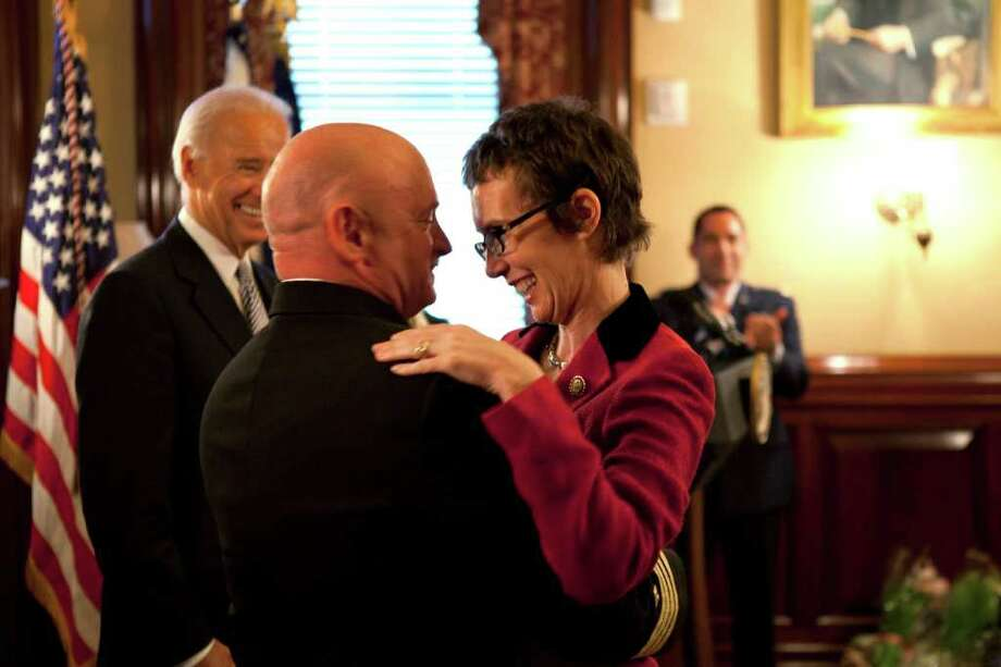 In this photo released by the White House, Navy Capt. Mark Kelly hugs his wife, Rep. Gabrielle Giffords, after Vice President Joe Biden officiates at the astronaut's retirement. Photo: David Lienemann / The White Hosue