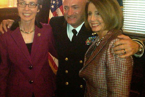 This image released by House Minority Leader Nancy Pelosi's office, shows Rep. Gabrielle Giffords, D-Ariz., left, and Pelosi, right, posing with Giffords husband, former astronaut Mark Kelly of the Navy, at his retirement ceremony with Vice President Joe Biden in the Old Executive Office Building on the White House complex in Washington, Thursday, Oct. 6, 2011. The visit marks Giffords second trip to Washington since she was shot in the head last January while meeting with constituents in her district. Aides said Giffords planned to conduct no congressional business and would return to Houston shortly after the ceremony to continue her rehabilitation. (AP Photo/House Leader Nancy Pelosi's office)