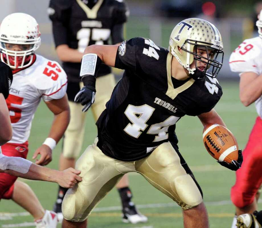 Trumbull High School running back Don Cherry, # 44 breaks a run upfield while being pursued by Kyle Camacho of Greenwich High School, # 55, during high school football game between Greenwich High School and Trumbull High School at Trumbull High School, Thursday night, Oct. 6, 2011. Photo: Bob Luckey / Greenwich Time