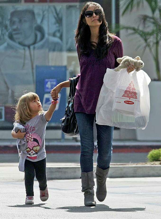 In this Sept. 29, 2011 photo, a woman and child leave a mall with purchases in Culver City, Calif. Americans shopped in September, but only when they thought they were getting a deal. (AP Photo/Reed Saxon) Photo: Reed Saxon
