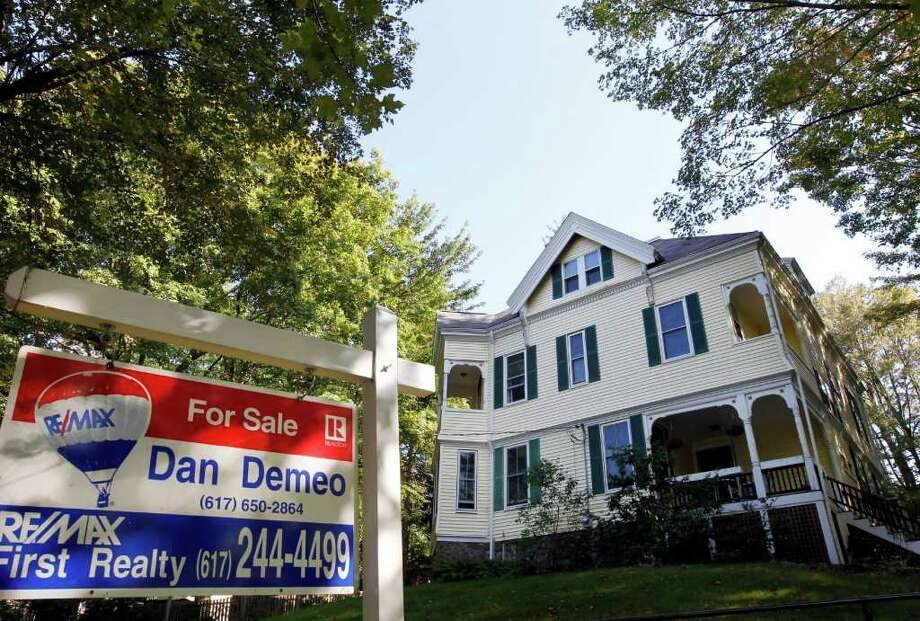This photo taken Sept. 19, 2011, shows a home with a for sale sign in front, in Newton, Mass. The average rate on the 30-year fixed mortgage fell to 3.94 percent this week, the lowest rate ever. For those who can qualify, it's an extraordinary opportunity to buy or refinance. (AP Photo/Steven Senne) Photo: Steven Senne