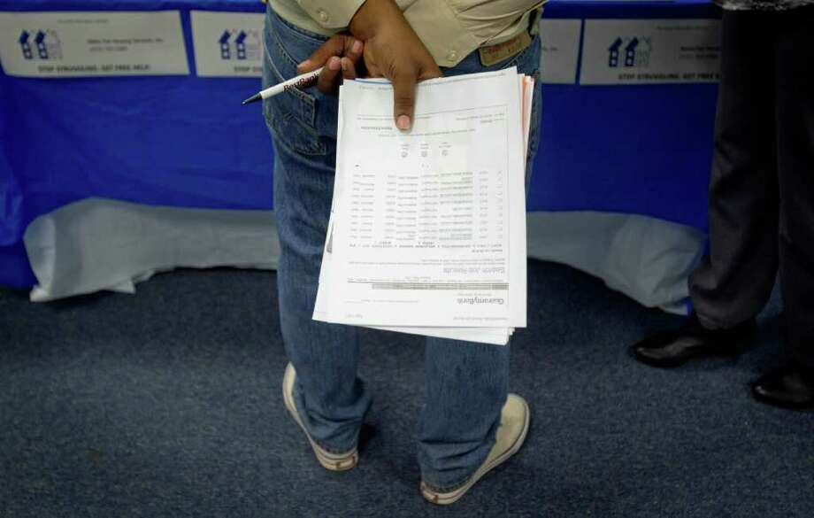 In this Oct. 4, 2011 photo, a job seeker holds a list of employment openings while talking with a recruiter during a job fair at a Goodwiill store, in Atlanta. The number of people who applied for unemployment benefits rose slightly last week, a sign that the job market remains weak. (AP Photo/David Goldman) Photo: David Goldman