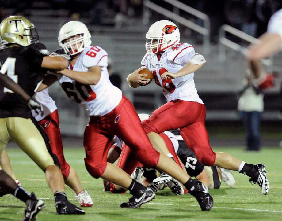 At left, Jackson Dell'abate, # 60 of Greenwich High School, opens up a hole for teammate, Shane Nastahowski, right, # 48, during football game between Greenwich High School and Trumbull High School at Trumbull High School, Thursday night, Oct. 6, 2011. Photo: Bob Luckey / Greenwich Time