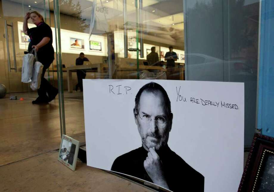 A portrait of Steve Jobs hangs on the window of an Apple Store, Thursday, Oct. 6, 2011, in Las Vegas. Jobs, the Apple founder and former CEO who invented and masterfully marketed gadgets that transformed everyday technology, from the personal computer to the iPod and iPhone, died Wednesday. He was 56. (AP Photo/Julie Jacobson) Photo: Julie Jacobson