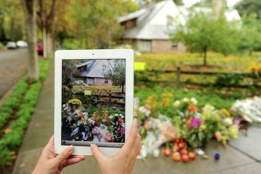 Using an iPad, Rebecca Lee photographs a memorial outside Steve Job's Palo Alto, Calif., home on Thursday, Oct. 6, 2011. The Apple co-founder and former CEO died Wednesday, at age 56. (AP Photo/Noah Berger) Photo: Noah Berger