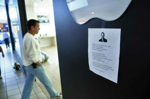 A memorial to the late Steve Jobs was taped to the entrance of the Apple Store at Crossgates Mall on Thursday Oct. 6, 2011 in Guilderland, NY.  The Apple co founder died on Wednesday. A store employee said that the apple logos outside of the store weren't lit, for the first time in his memory. ( Philip Kamrass / Times Union) Photo: Philip Kamrass / 00014892A