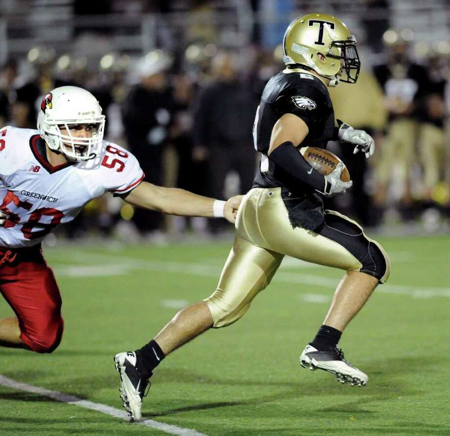 At left, Alex McGee, # 58 of Greenwich High School, misses a tackle on Ryan Pearson, # 2 of Trumbull High School, on a long kick-off return by Pearson during high school football game between Greenwich High School and Trumbull High School at Trumbull High School, Thursday night, Oct. 6, 2011. Photo: Bob Luckey / Greenwich Time