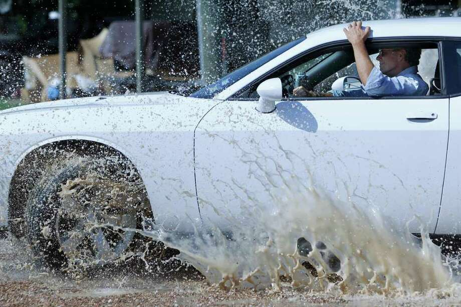 "John Schneider, an actor in the TV show Dukes of Hazard, drives over puddles while shooting the new reality series ""Trick My What?"" for the cable network Country Music Television in Richmond.  The crew films at the Lonestar Speed Shop where they'll overhaul a tractor or steamroller. Photo: Mayra Beltran, Houston Chronicle / © 2011 Houston Chronicle"