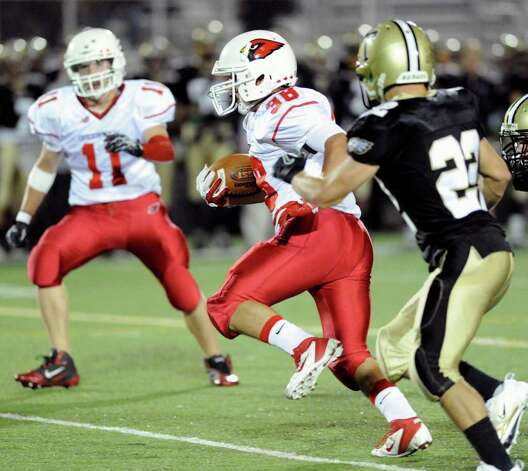 Running back Dan Claroni, # 38 of Greenwich High School, beats Trumbull defender Bill O'Keefe, # 22, during high school football game between Greenwich High School and Trumbull High School at Trumbull High School, Thursday night, Oct. 6, 2011.  At left is Alex McMurray, # 11 of Greenwich. Photo: Bob Luckey / Greenwich Time