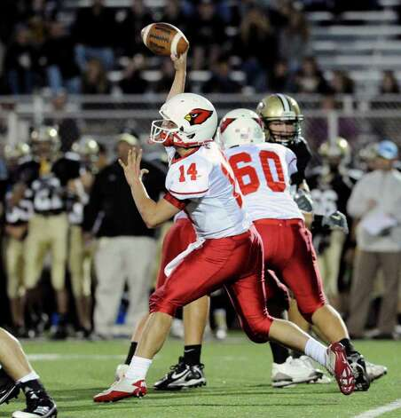 Quarterback Liam O'Neil, # 14 of Greenwich High School, throws while getting blocking from teammate, Jackson Dell'abate, # 60, during high school football game between Greenwich High School and Trumbull High School at Trumbull High School, Thursday night, Oct. 6, 2011. Photo: Bob Luckey / Greenwich Time