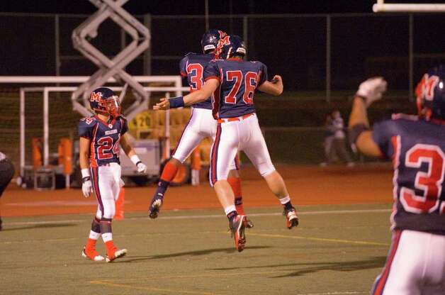 McMahon's Chris Jerome, left, and Danny Medico celebrate a touchdown as Brien McMahon hosts New Canaan High School in a football game October 6, 2011. Photo: Keelin Daly / Stamford Advocate