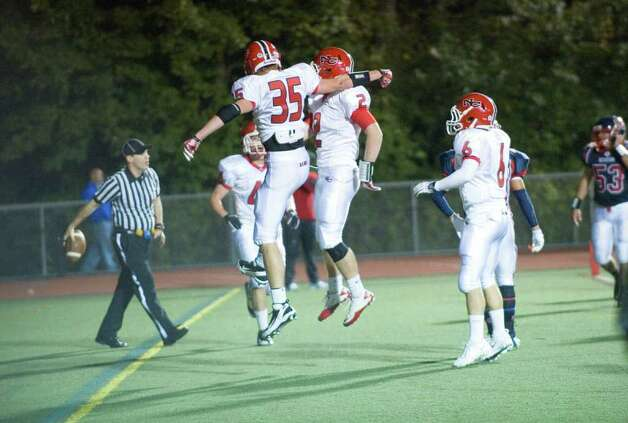 New Canaan's John Brainard, left, and Peter Kraus celebrate a touchdown as Brien McMahon hosts New Canaan High School in a football game October 6, 2011. Photo: Keelin Daly / Stamford Advocate