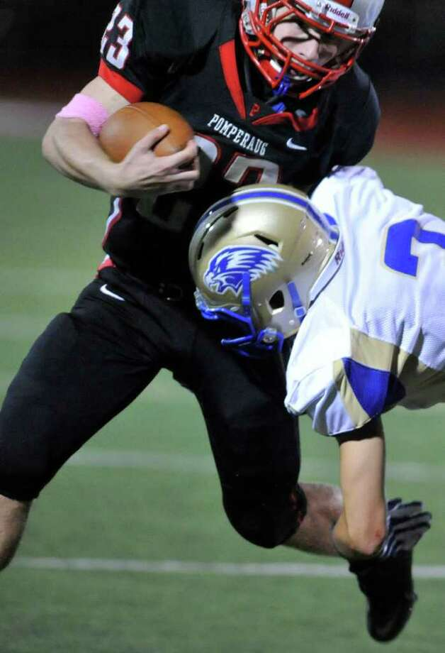Pomperaug's Dylan McAllister, top, tries to evade the hit of Newtown's Chris Devaney during their game at Pomperaug High School in Southbury on Thursday, Oct. 6, 2011. Photo: Jason Rearick / The News-Times