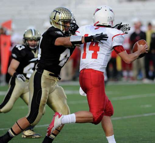 Don Cherry of Trumbull, #44, left, sacks Greenwich HIgh School quarterback, Liam O'Neil, # 14, during high school football game between Greenwich High School and Trumbull High School at Trumbull High School, Thursday night, Oct. 6, 2011. Photo: Bob Luckey / Greenwich Time