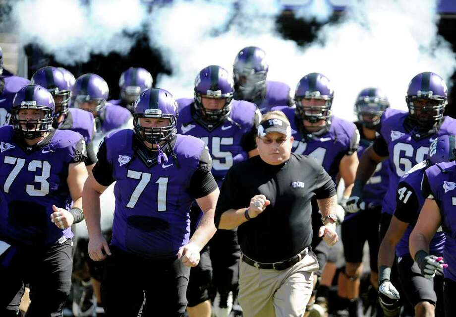 In this photo taken Saturday, Oct. 1, 2011, TCU head coach Gary Patterson runs onto the field with his team before an NCAA college football game against SMU in Fort Worth, Texas. Leaders of the Big 12 Conference cleared the way Thursday, Oct. 6, 2011, to add TCU, a move that would bring in a rising program and potentially shore up a league that seemed ready to fall apart just a few weeks ago. (AP Photo/Matt Strasen) Photo: Matt Strasen, Associated Press / AP2011