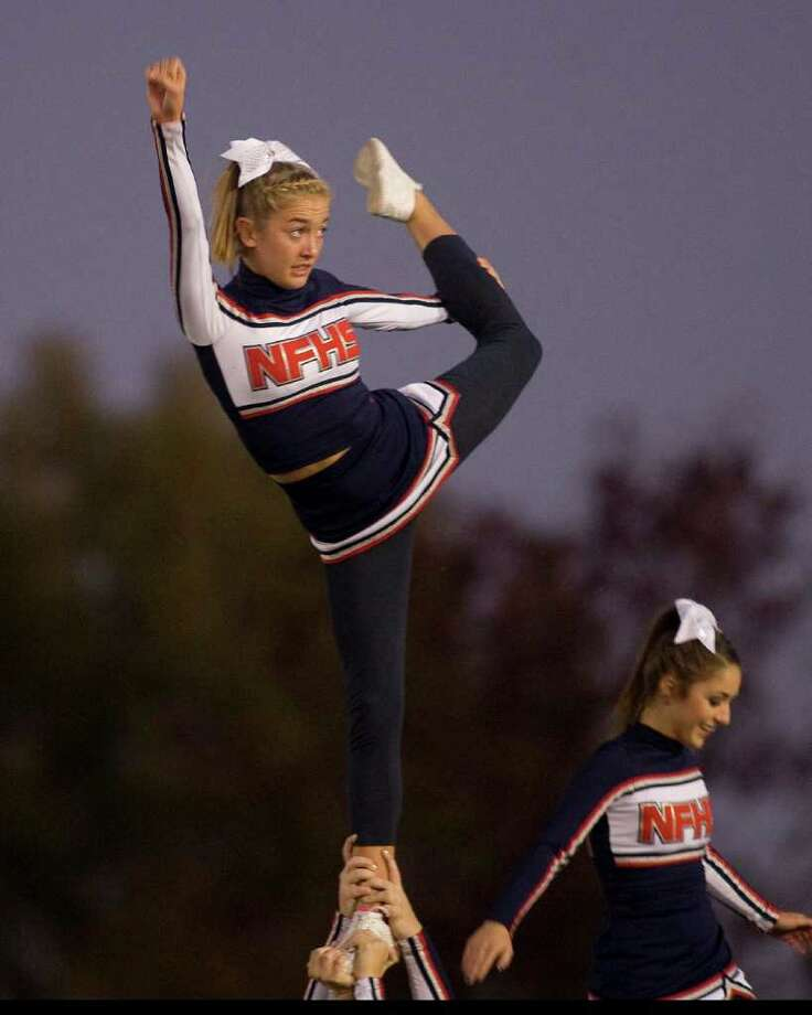A New Fairfield High School cheerleader practices before the Rebels' SWC football game against Brookfield High School Friday night, Oct. 6, 2011, at New Fairfield High School. Photo: Barry Horn