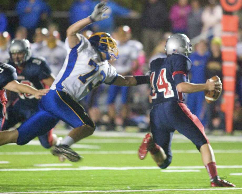 Brookfield High School's Joel Wamser closes in on New Fairfield High School quarterback Mike Jamieson during their SWC football game Friday night, Oct. 6, 2011, at New Fairfield High School. Photo: Barry Horn / The News-Times Freelance