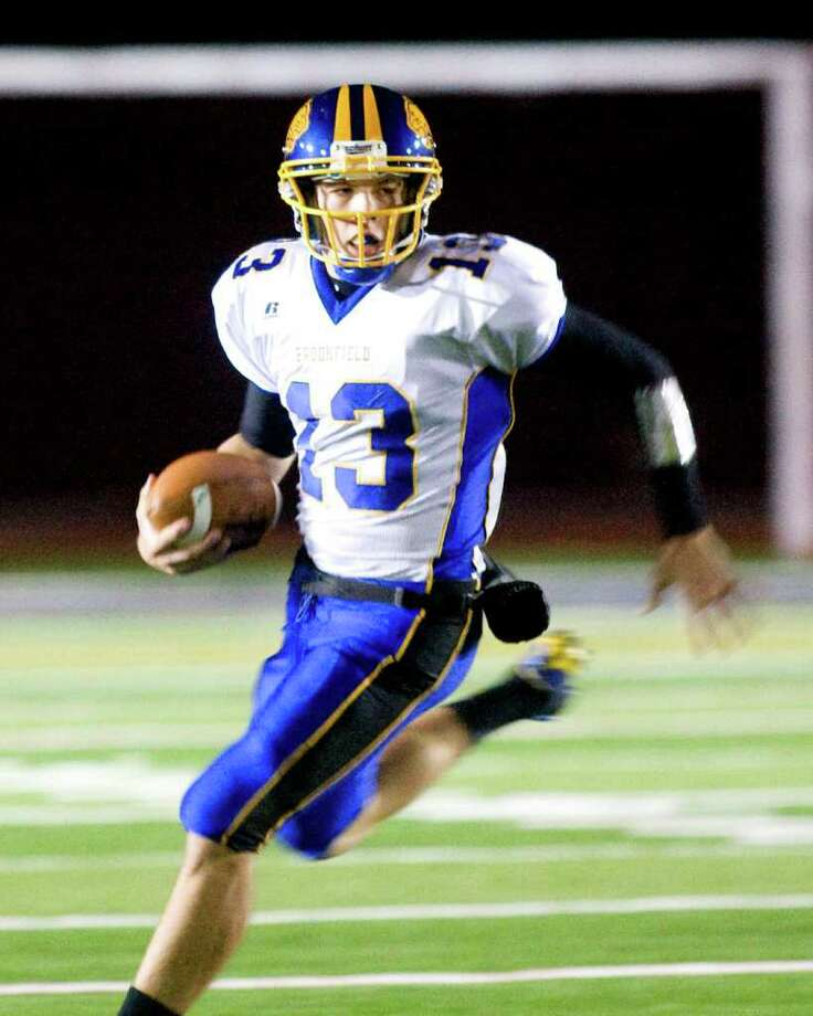 Brookfield High School quarterback Boeing Brown rolls out around end during an SWC football game against New Fairfield High School Friday night, Oct. 7, 2011, at New Fairfield High School. Photo: Barry Horn / The News-Times Freelance