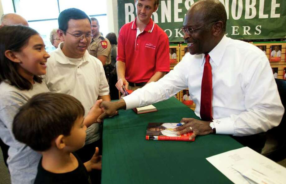 Republican presidential hopeful Herman Cain, right, shakes hands with Mia Vu as he autographs books at the Barnes & Noble bookstore Thursday, Oct. 6, 2011, in The Woodlands. Standing with Mia are her father, The', and her brother Quyen. Photo: Brett Coomer, Houston Chronicle / © 2011 Houston Chronicle