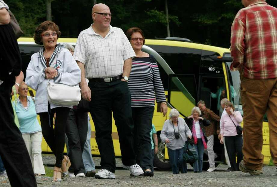 In this Sept. 23, 2011 photo, tourists from England get off a bus at the Morse Farm Maple Sugarworks in East Montpelier, Vt. Although Vermont is still working to repair roads in the aftermath of Tropical Storm Irene, a coalition of Vermont tourism interests are underscoring that three weeks have gone by since the storm, and about 95 percent of the state's roads are open for tourists to enjoy the start of fall foliage season and other outdoor activities and festivals. (AP Photo/Toby Talbot) Photo: Toby Talbot