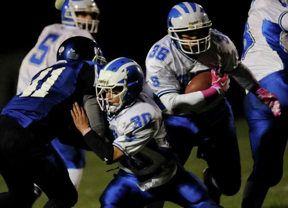 Shaker's Jared Kirkey (36), right, runs the ball as teammate Kyle Bernard (30), center, blocks  LaSalle's Devar Jones (41) during their football game on Thursday, Oct. 6, 2011, at LaSalle Institute in Troy, N.Y. (Cindy Schultz / Times Union) Photo: Cindy Schultz