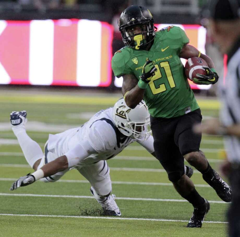 DON RYAN: ASSOCIATED PRESS ONE-MAN JAMES GANG: Oregon running back LaMichael James, right, evades California defender Sean Cattouse on his way to scoring a touchdown in the first half of Thursday's game. Photo: Don Ryan / AP