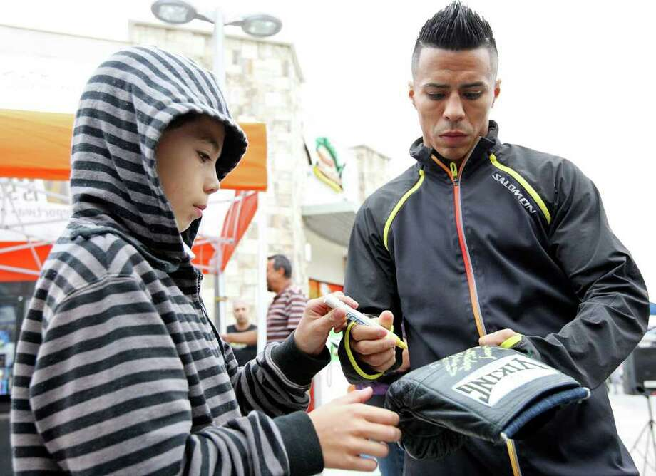 Emmanuel Velasco, 9, (left) gets an autograph from Raul Martinez Wednesday Oct. 5, 2011 in Tijuana, Baja California, Mexico.  Martinez will fight Rodrigo Guerrero (not pictured) for the IBF super flyweight title Saturday Oct. 8 in Tijuana.  (PHOTO BY EDWARD A. ORNELAS/eaornelas@express-news.net) Photo: EDWARD A. ORNELAS, SAN ANTONIO EXPRESS-NEWS / © SAN ANTONIO EXPRESS-NEWS (NFS)