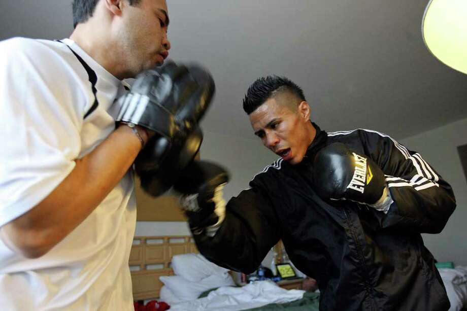 Jesus Chavez (left) works out with Raul Martinez in a room at the Palacio Azteca Hotel in Tijuana, Baja California, Mexico Thursday Oct. 6, 2011. Martinez will fight Rodrigo Guerrero for the IBF super flyweight title Saturday Oct. 8 in Tijuana.   (PHOTO BY EDWARD A. ORNELAS/eaornelas@express-news.net) Photo: EDWARD A. ORNELAS, SAN ANTONIO EXPRESS-NEWS / © SAN ANTONIO EXPRESS-NEWS (NFS)