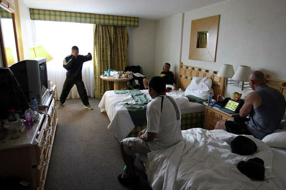 Raul Martinez (from left) works out in a room at the Palacio Azteca Hotel in Tijuana, Baja California, Mexico Thursday Oct. 6, 2011 as members of Team Cobrita trainer Jesus Chavez,  cutman Joe Villanueva, and conditioning coach Tony Cooper look on. Martinez will fight Rodrigo Guerrero for the IBF super flyweight title Saturday Oct. 8 in Tijuana.   (PHOTO BY EDWARD A. ORNELAS/eaornelas@express-news.net) Photo: EDWARD A. ORNELAS, SAN ANTONIO EXPRESS-NEWS / © SAN ANTONIO EXPRESS-NEWS (NFS)