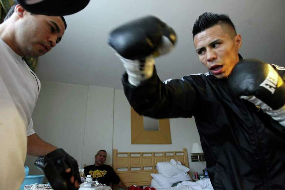 Trainer Jesus Chavez (left) works out with Raul Martinez in a room at the Palacio Azteca Hotel in Tijuana, Baja California, Mexico Thursday Oct. 6, 2011 as cutman Joe Villanueva (background center) looks on. Martinez will fight Rodrigo Guerrero for the IBF super flyweight title Saturday Oct. 8 in Tijuana.   (PHOTO BY EDWARD A. ORNELAS/eaornelas@express-news.net) Photo: EDWARD A. ORNELAS, SAN ANTONIO EXPRESS-NEWS / © SAN ANTONIO EXPRESS-NEWS (NFS)