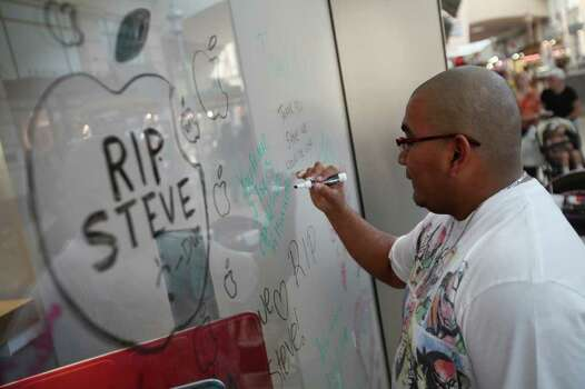 Phillip Reyes writes a message outside the Apple store in honor of Jobs, co-founder and former chief executive officer of Apple Inc.,  at Memorial City Mall in Houston on Thursday, Oct. 6, 2011. Photo: Mayra Beltran/Houston Chronicle