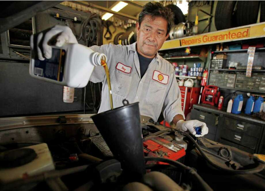 In this Oct. 4, 2011 photo, mechanic Ray Duran changes oil in a car at a Shell station in Los Angeles. Employers added 103,000 jobs in September, a modest burst of hiring after a sluggish summer. (AP Photo/Reed Saxon) Photo: Reed Saxon / AP