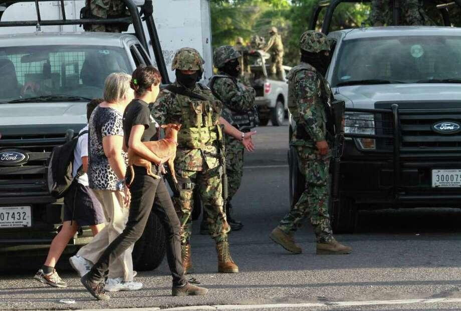 Dos mujeres caminan junto a un grupo de Infantes de Marina de México en Boca del Río, Veracruz, el 6 de octubre de 2011, donde fueron encontrados 32 cuerpos de una nueva matanza relacionada al narcotráfico. Photo: LUCAS CASTRO / AFP
