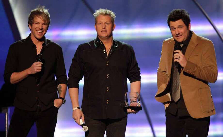 In this April 4, 2011, photo, from left, Joe Don Rooney, Gary LeVox and Jay DeMarcus, of the musical group Rascal Flatts, present an award to honoree Reba McEntire at the Girls' Night Out: Superstar Women of Country in Las Vegas. (AP Photo/Julie Jacobson) Photo: Julie Jacobson / AP2011