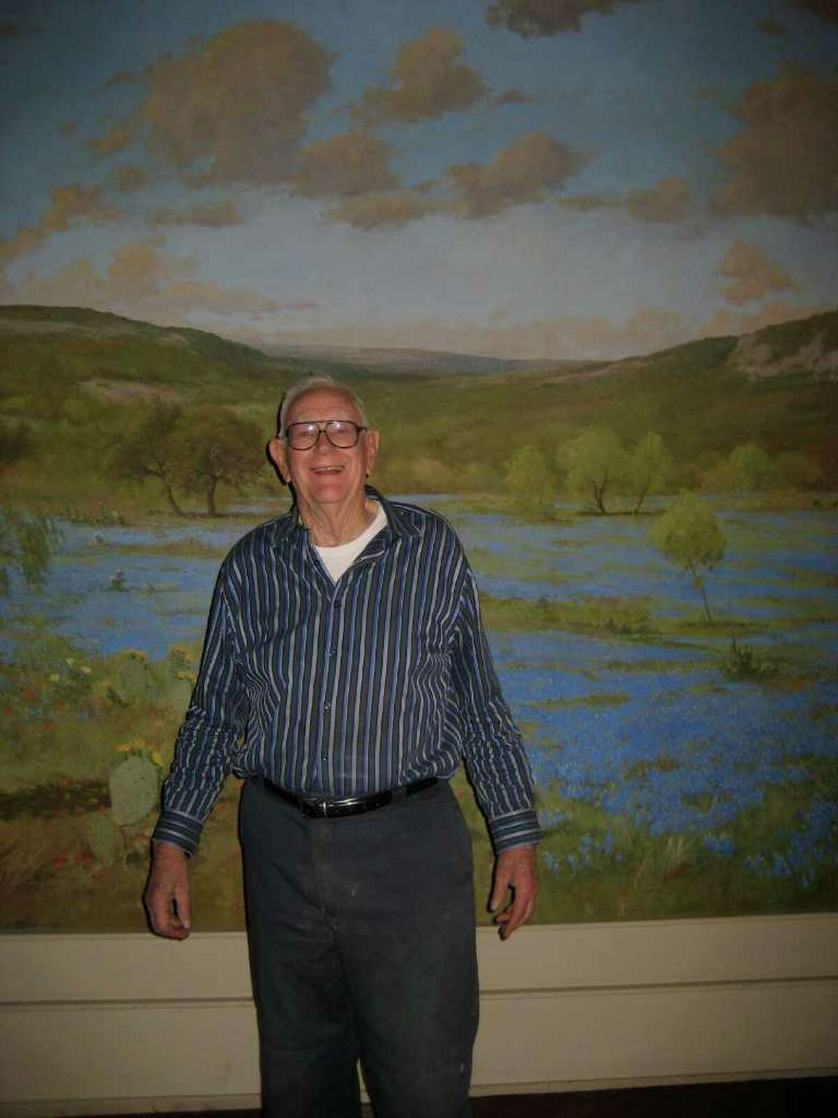 The 30-foot-wide mural of a bluebonnet field by prominent Hill Country painter Porfirio Salinas (1910Ð1973) may have survived the fire at the Wolfson Building. The Carter family hopes it will be donated to the Witte Museum. Here is David Carter in front on the painting.
