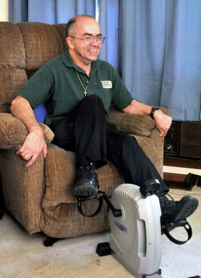Terry Thompson, 48, uses a mechanical excerciser in his Danbury home Friday, Oct. 7, 2011. Photo: Michael Duffy