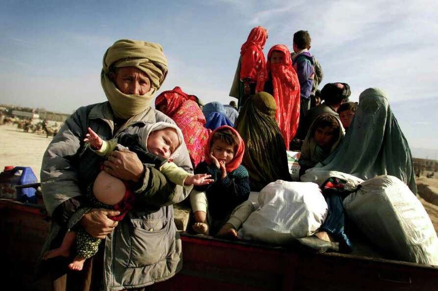 Internally displaced persons prepare to relocate as U.S. planes and special forces begin an assault
