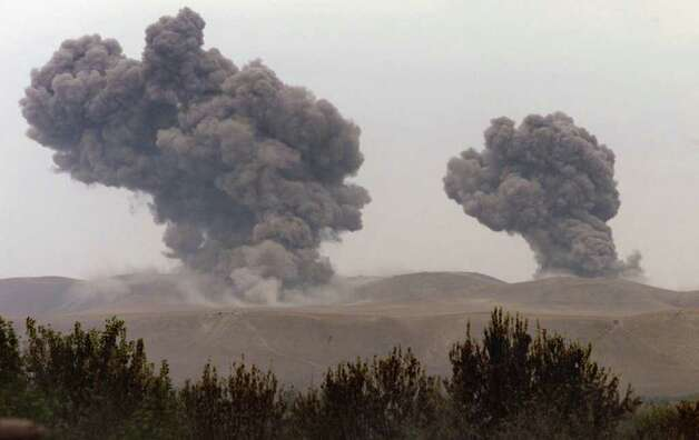 Bombs from a U.S. B-52 kick off an assault against the Taliban in northern Afghanistan, hitting Taliban tank positions in this October 2001 photo. Photo: JOSHUA TRUJILLO / SEATTLEPI.COM