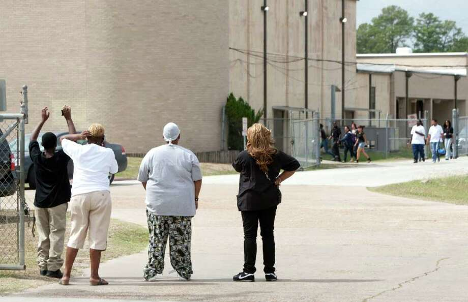 Parents of North Forest High School students stand outside the fence of the school during a lockdown where there were reports of a student with a gun Friday, Oct. 7, 2011, in Houston. North Forest High School officials lifted a lockdown shortly after noon Friday after finding no student with gun on campus, school officials said. Photo: Brett Coomer, Houston Chronicle / © 2011 Houston Chronicle