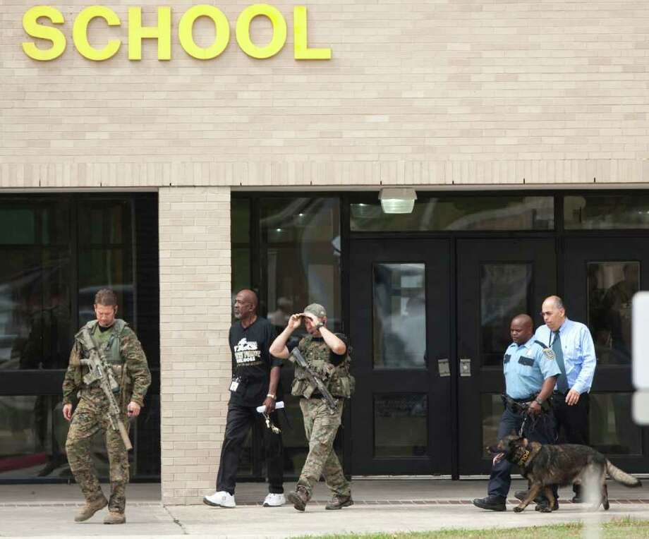 Police officials patrol outside North Forest High School during a lockdown where there were reports of a student with a gun Friday, Oct. 7, 2011, in Houston. North Forest High School officials lifted a lockdown shortly after noon Friday after finding no student with gun on campus, school officials said. Photo: Brett Coomer, Houston Chronicle / © 2011 Houston Chronicle