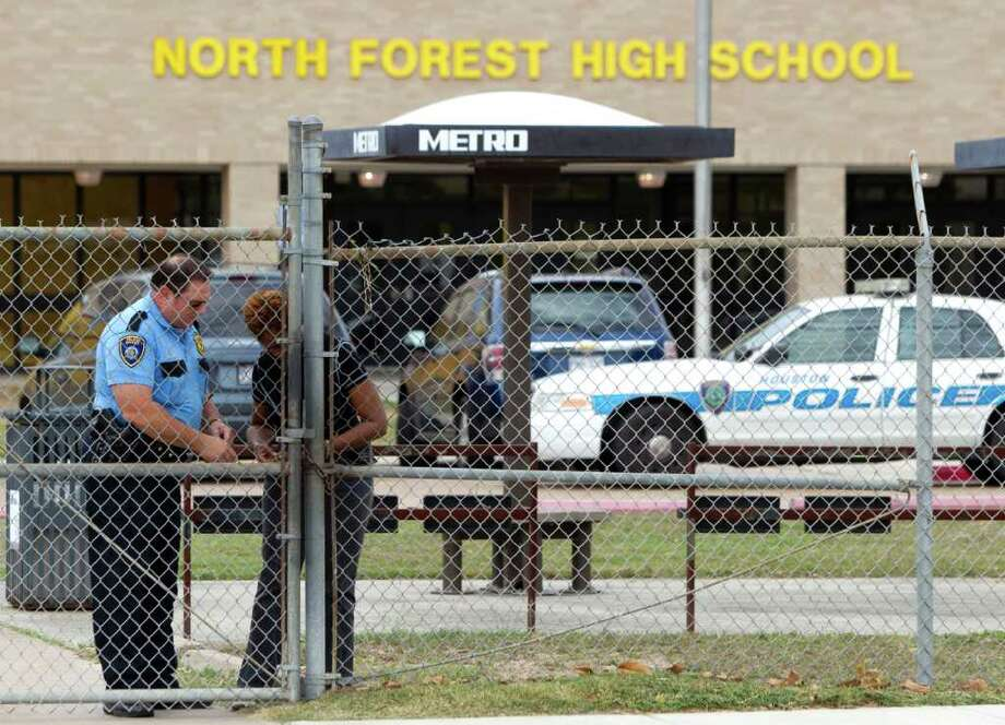 Police and school officials lock a gate outside North Forest High School during a lockdown where there were reports of a student with a gun Friday, Oct. 7, 2011, in Houston. North Forest High School officials lifted a lockdown shortly after noon Friday after finding no student with gun on campus, school officials said. Photo: Brett Coomer, Houston Chronicle / © 2011 Houston Chronicle