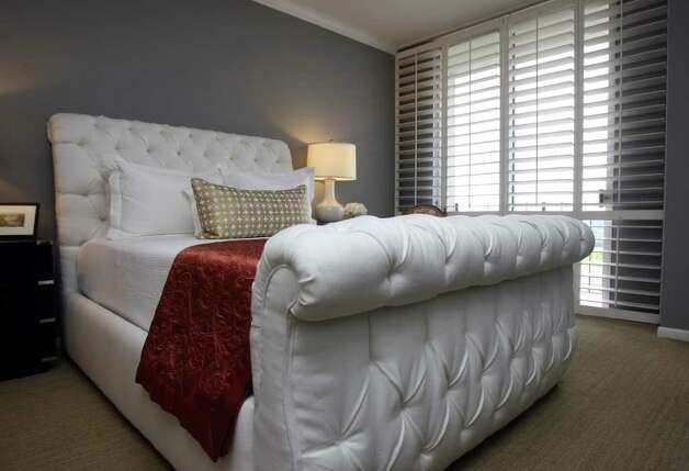 The custom bed frame in the master bedroom is covered in tufted linen. A colorful throw enlivens the sophisticated palette. Photo: HELEN L. MONTOYA, San Antonio Express-News / SAN ANTONIO EXPRESS-NEWS