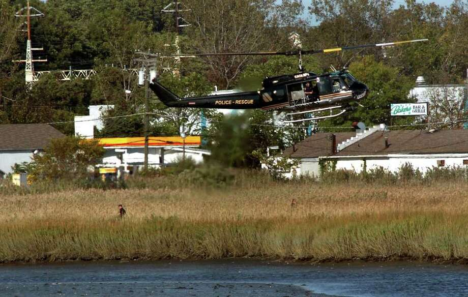 A Milford Police Department helicopter hovers low as officers search wetland off of New Haven Avenue during a manhunt for a fugitive in Milford, Conn. on Friday, Oct. 7th, 2011. Photo: Christian Abraham / Connecticut Post
