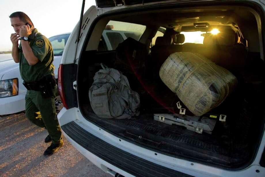 Un agente de la Patrulla Fronteriza de Estados Unidos camina junto a un automóvil que tiene un paquete de marijuana confiscado en un cruce del Río Grande a Hidalgo, Texas, desde Reynosa, México. Photo: Johnny Hanson / Houston Chronicle