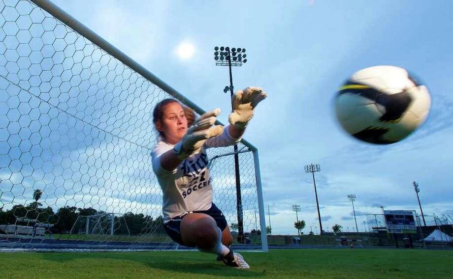 La guardavallas Gaby Garton, quien fue invitada a representar internacionalmente a Argentina, el país de sus padres, se arroja para rechazar el balón durante un entrenamiento en el campus de la Universidad de Rice en Houston. Photo: Cody Duty / © 2011 Houston Chronicle