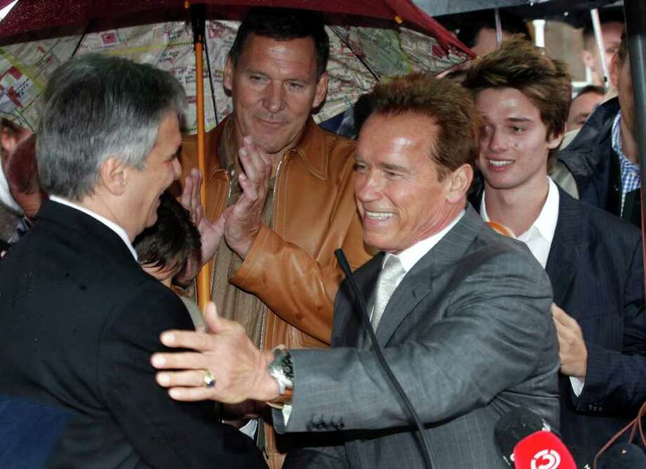 Austrian-born actor and former Californian governor, Arnold Schwarzenegger, right, is welcomed by Austrian chancellor Werner Faymann, left, while German actor Ralf Moeller, center, applauds prior to the inauguration of a museum in the house of Schwarzenegger's birth in Thal near Graz, Austria Friday Oct. 7, 2011.  (AP Photo/dapd/ Markus Leodolter) Photo: Markus Leodolter / dapd