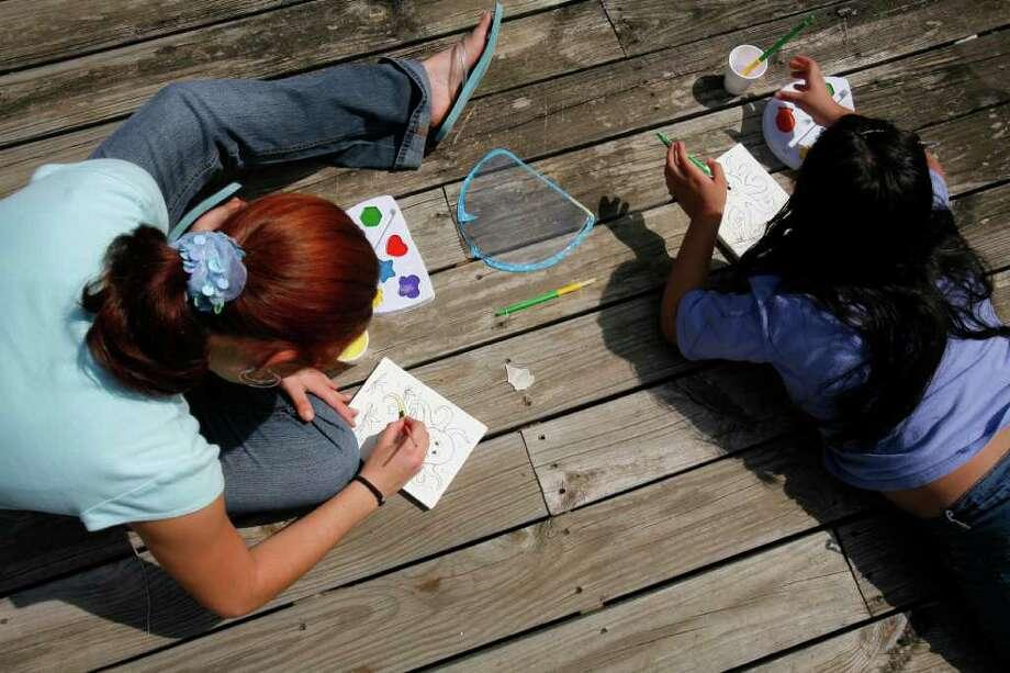 Dos niñas pintan y dibujan en el patio del albergue St. Michael de Caridades Católicas, en una imagen de hace varios años. Photo: Steve Campbell / Houston Chronicle