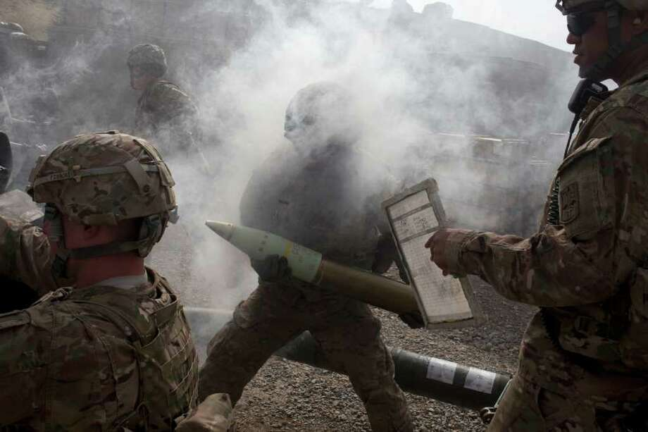 Tyler Hicks : The New York Times RETURNING FIRE: U.S. soldiers fire artillery rounds toward  an enemy rocket position beside the Pakistani border from Forward Operating Base Tillman in Afghanistan. Photo: TYLER HICKS / NYTNS